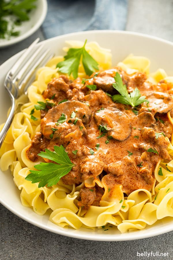 close up of ground beef stroganoff over pasta with fresh chopped parsley