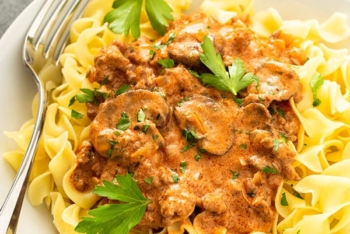 creamy beef and mushroom stroganoff sauce over cooked egg noodles in white bowl