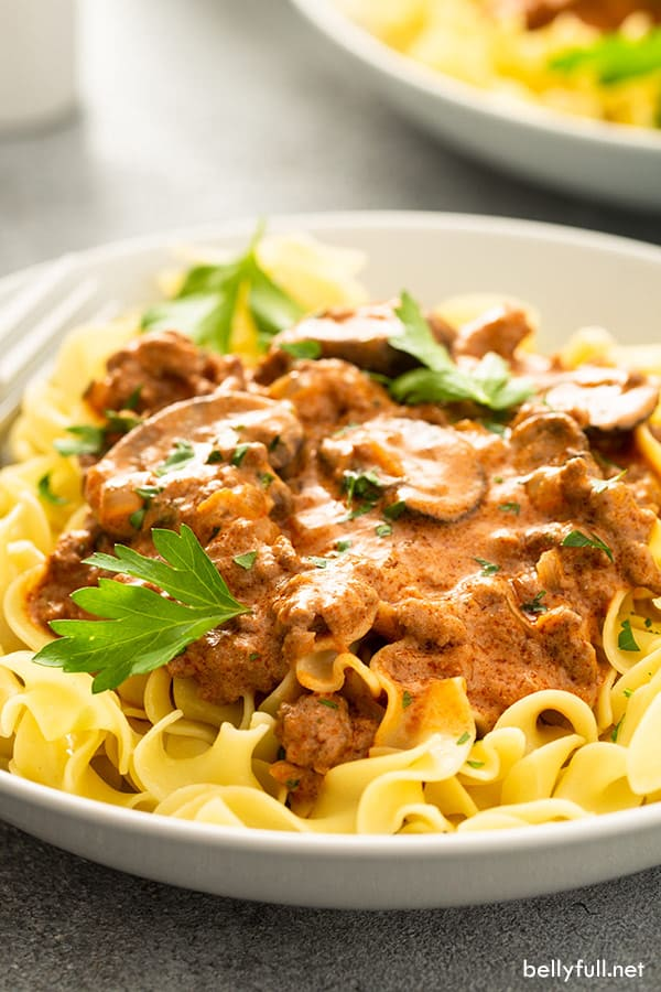 close up ground beef stroganoff over cooked egg noodles