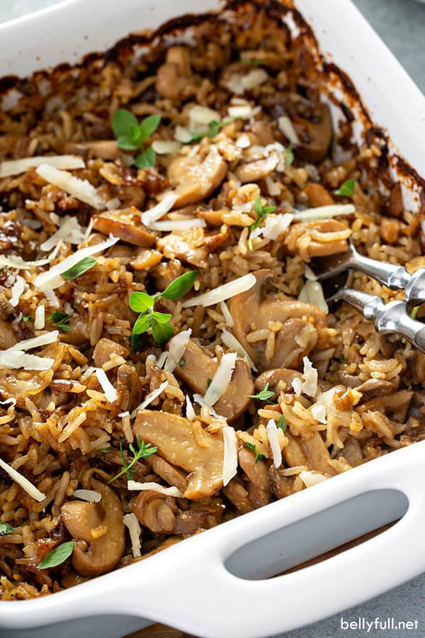 close up of cooked rice with mushrooms in white baking dish