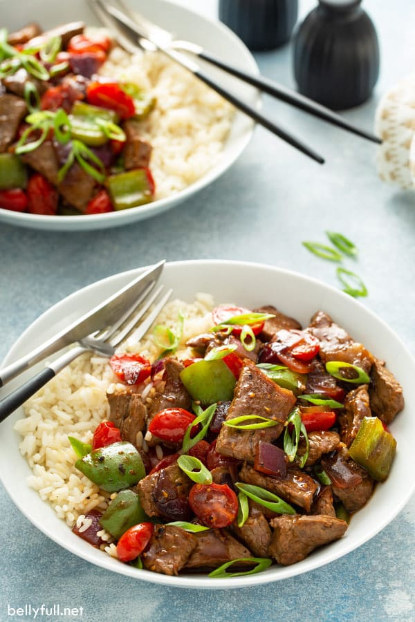 side angle of pepper steak with rice in white bowl