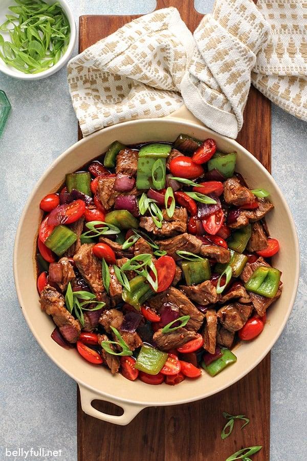overhead pepper steak ingredients in skillet