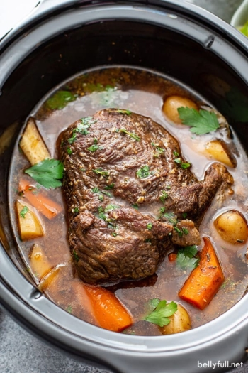 cooked chuck roast in crock pot with vegetables