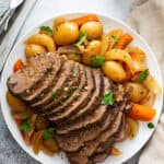 overhead sliced slow cooker pot roast and vegetables with gravy on white plate