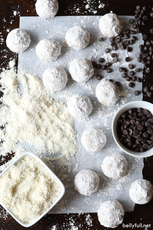 snowball cookies on parchment paper surrounded by chocolate chips and almond flour in bowls