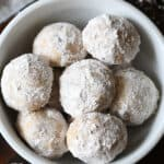 pile of pumpkin snowball cookies in white bowl