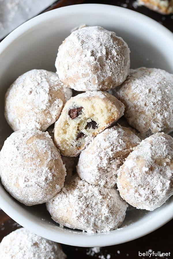snowball cookies in white bowl with one bitten into