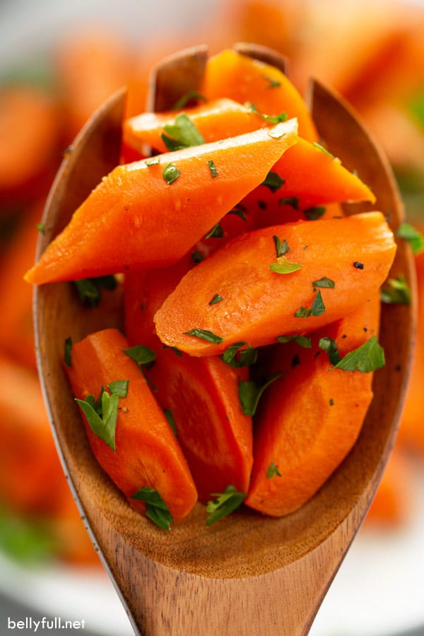 close up of roasted carrots on wooden spoon