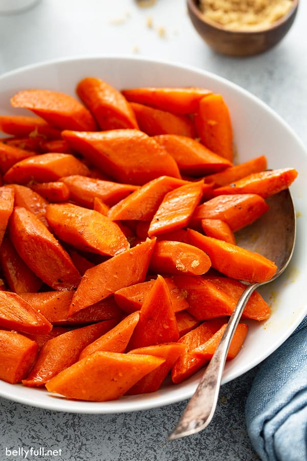 sliced roasted carrots in white serving bowl with spoon