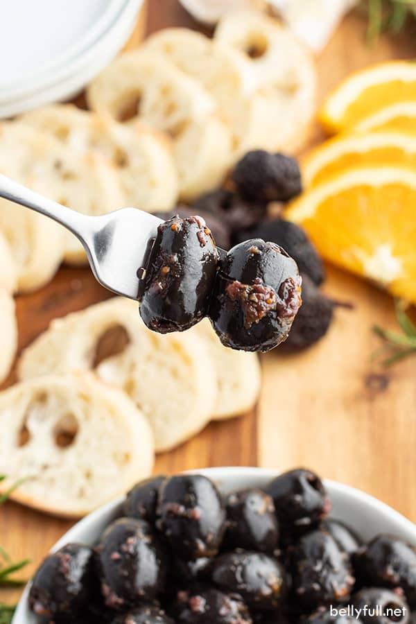 marinated black olives on fork close up