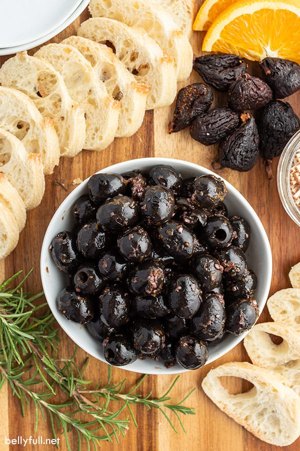 overhead of marinated black olives in white dish surrounded by crostini