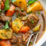 close up of beef stew in bowl with fork and spoon