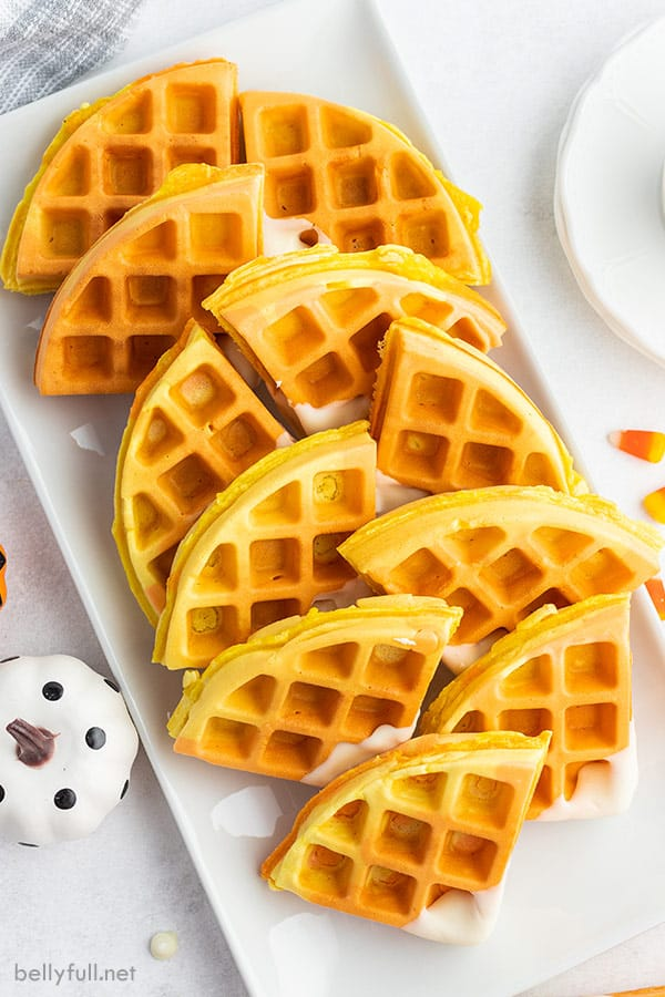 overhead of candy corn colored waffles on a white serving tray