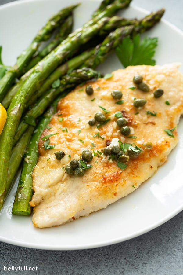 close up of chicken piccata on plate with roasted asparagus