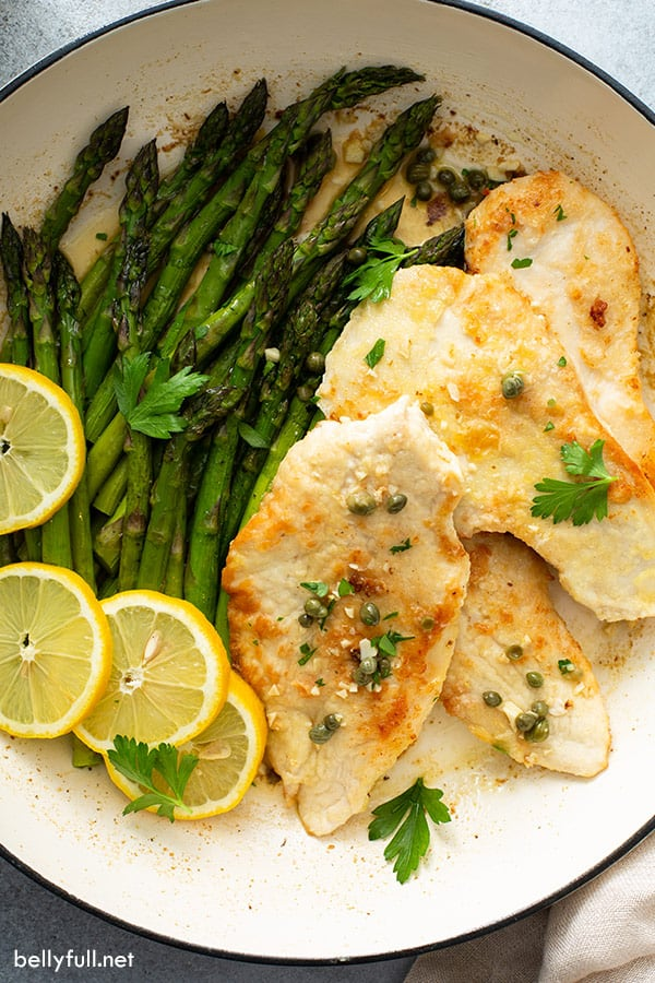 overhead of cooked breaded chicken cutlets and asparagus