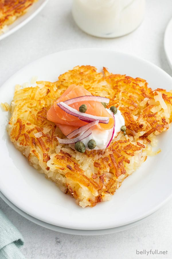 portion of hash browns on white plate topped with sour cream, lox, and capers