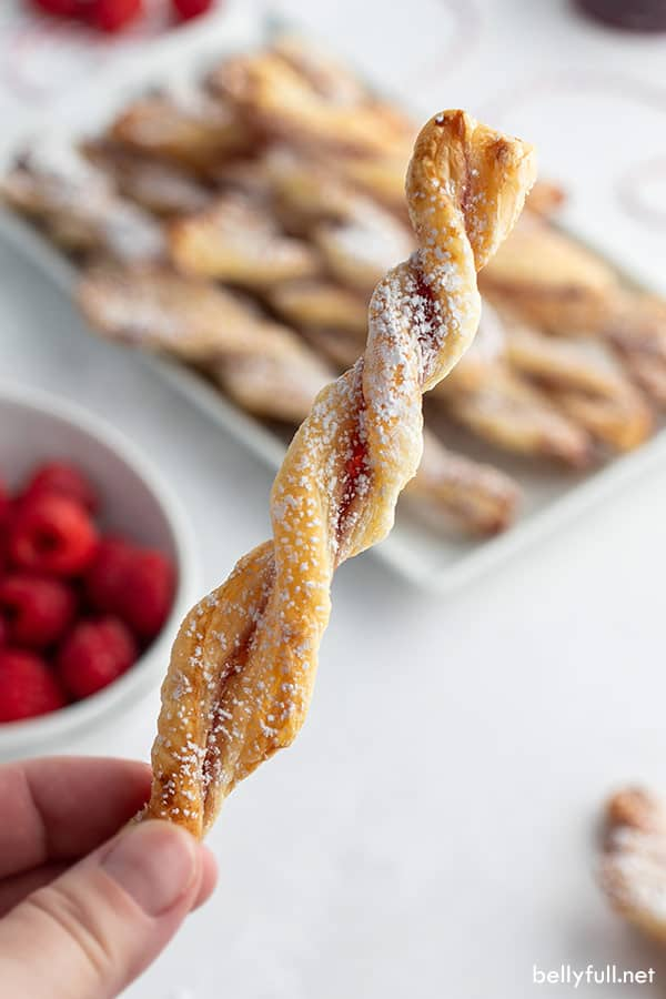 hand holding a single puff pastry jam straw