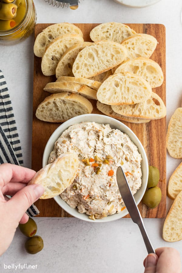 hands with bread and knife over bowl of olive dip