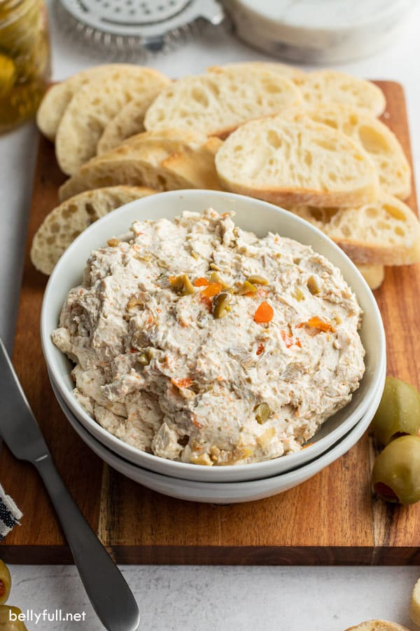 White bowl filled with olive spread and slice bread in the background