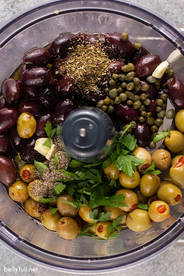 black and green olives, capers, and seasonings in food processor bowl