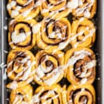 overhead of pan with pumpkin cinnamon rolls with icing