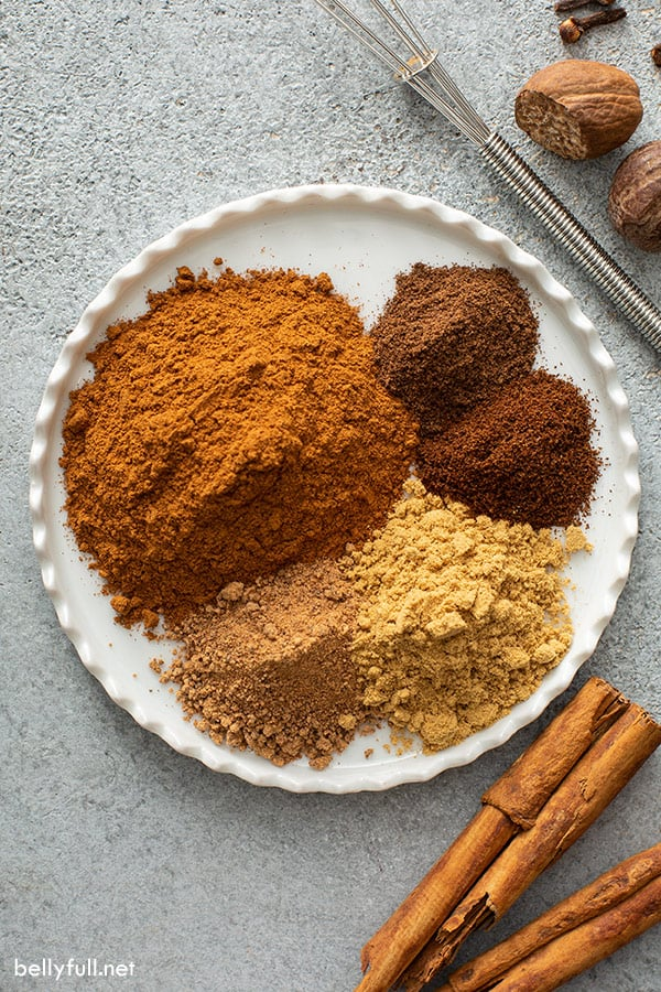 separated spices for pumpkin pie spice on white plate