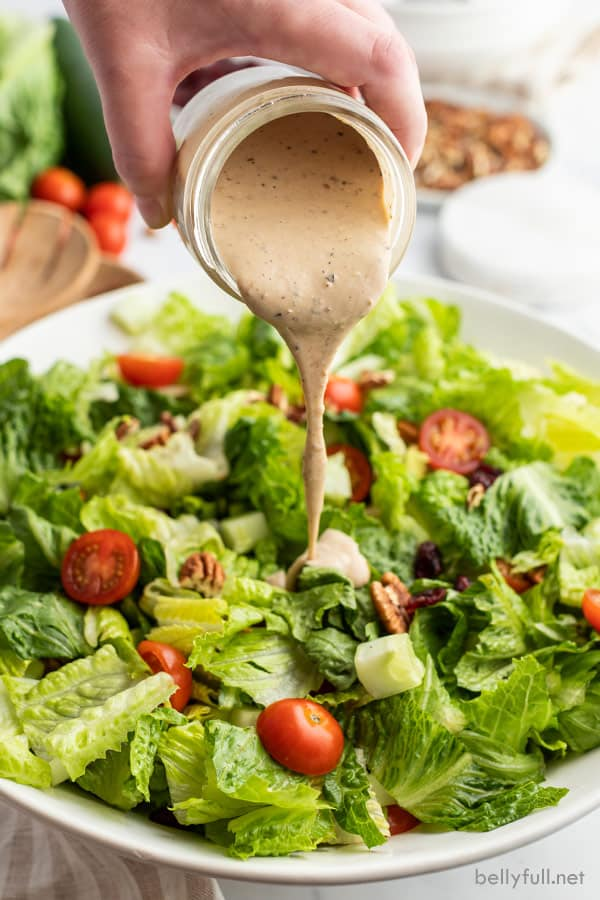 green salad with dressing being poured over it