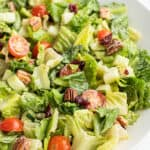 side salad mixed together with dressing in serving bowl