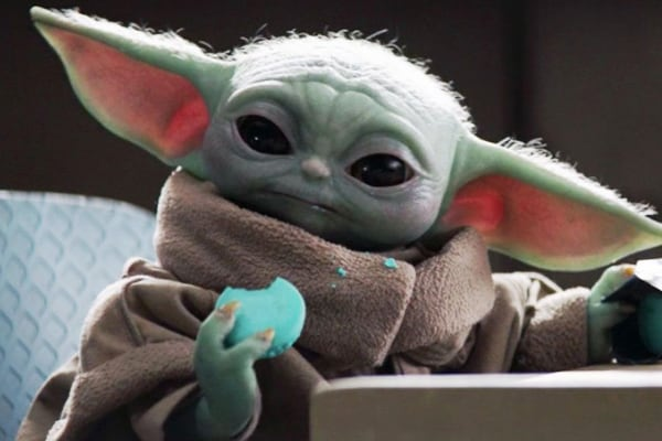 picture of baby yoda eating a blue space cookie