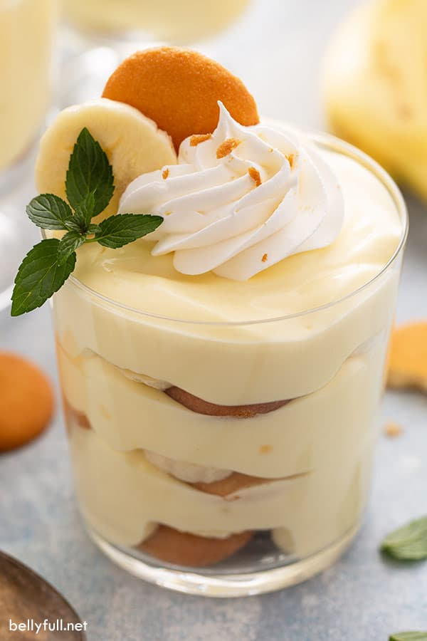 close up of banana pudding in a glass, garnished with whipped cream and a mint leaf