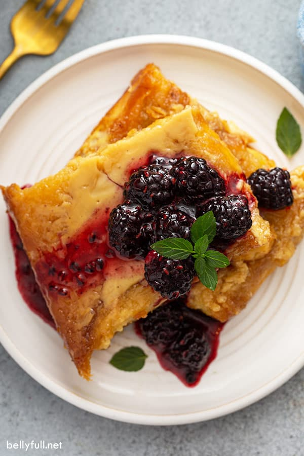 overhead of french toast on white plate, topped with sugared blackberries