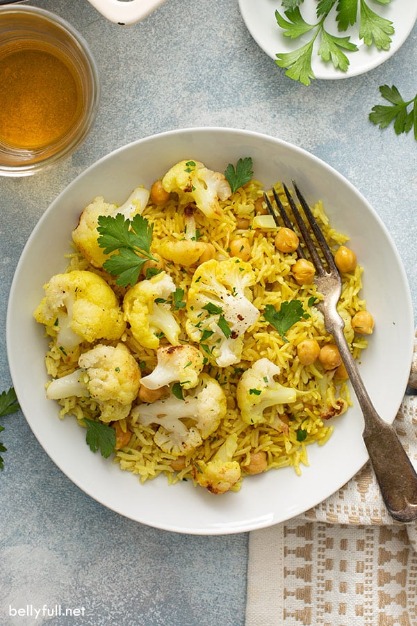 overhead of curried rice with cauliflower in white bowl with fork