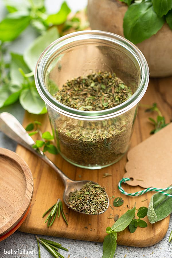 dried herbs on spoon and in jar
