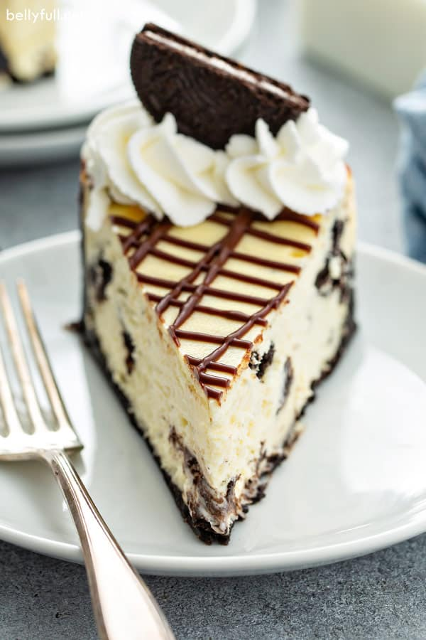 straight on close up picture of sliced Oreo cheesecake on white plate