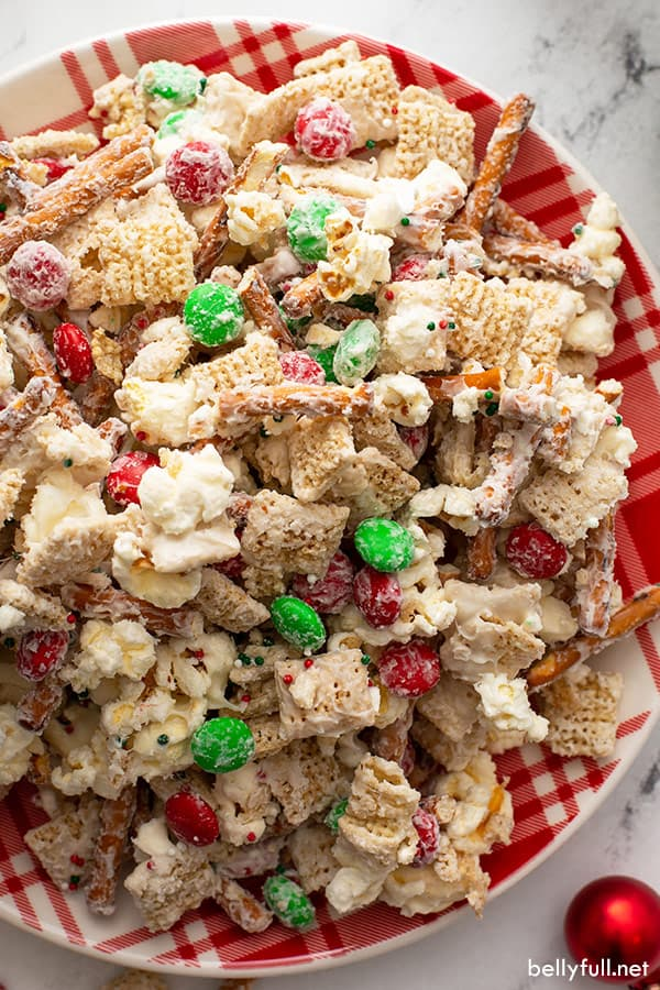 Close up overhead of Christmas Chex Mix on red and white plate