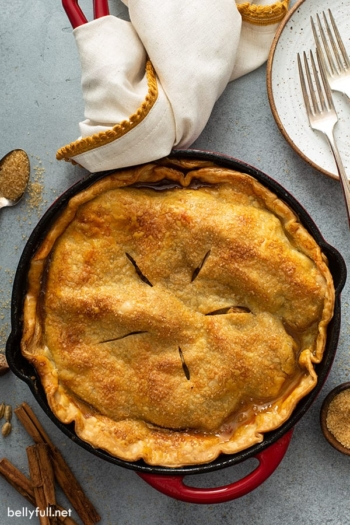 overhead of double crusted baked apple pie in cast iron skillet