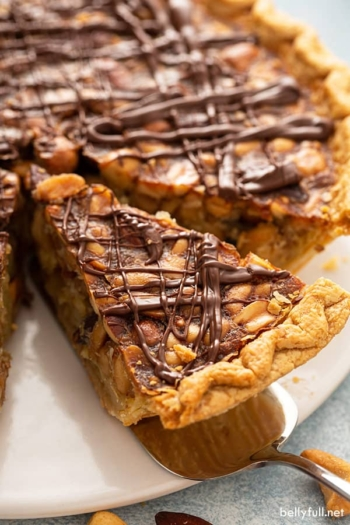 close up of slice of turtle pie drizzled with chocolate on serving spoon