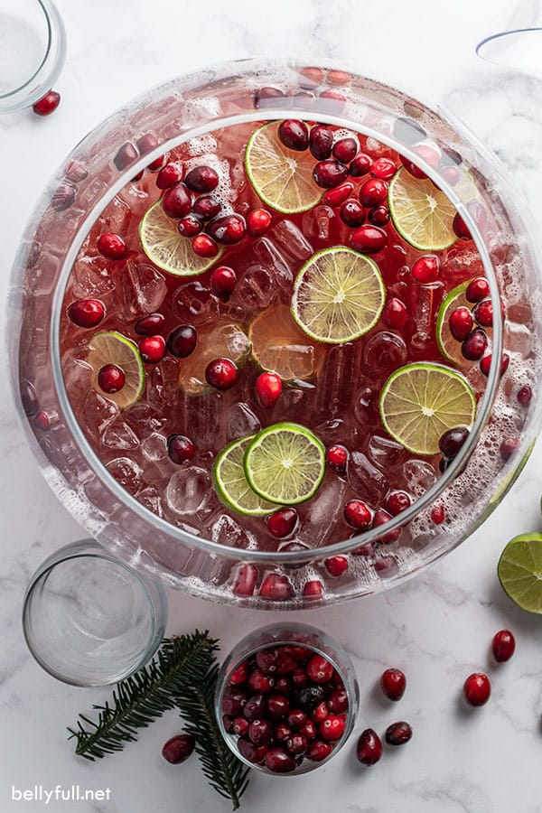 overhead holiday punch in big glass bowl with cranberries and lime slices