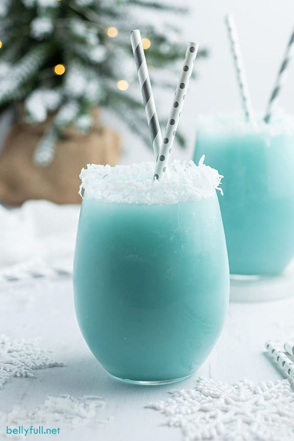 Blue snowy Winter Cocktail in glass with straw