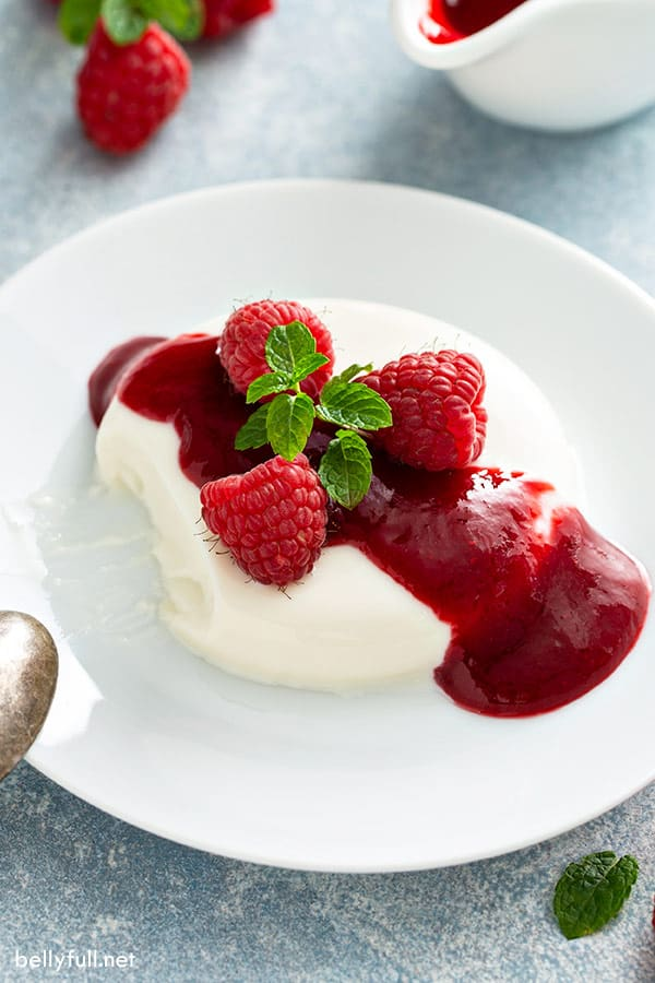 panna cotta unmolded onto white plate with raspberry sauce