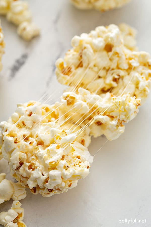 popcorn ball split in half with gooey stings of melted marshmallow