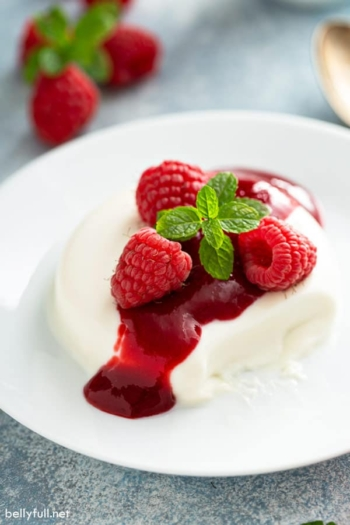 panna cotta with raspberry sauce and fresh mint leaves