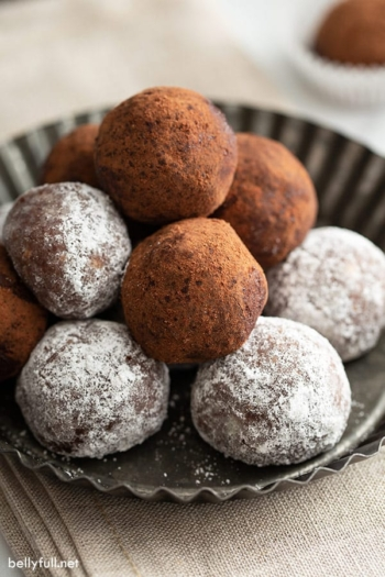 stack of rum balls coated in powdered sugar and cocoa powder