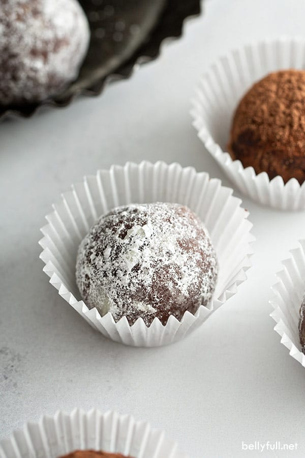 pecan chocolate truffle in mini paper liner coated with powdered sugar