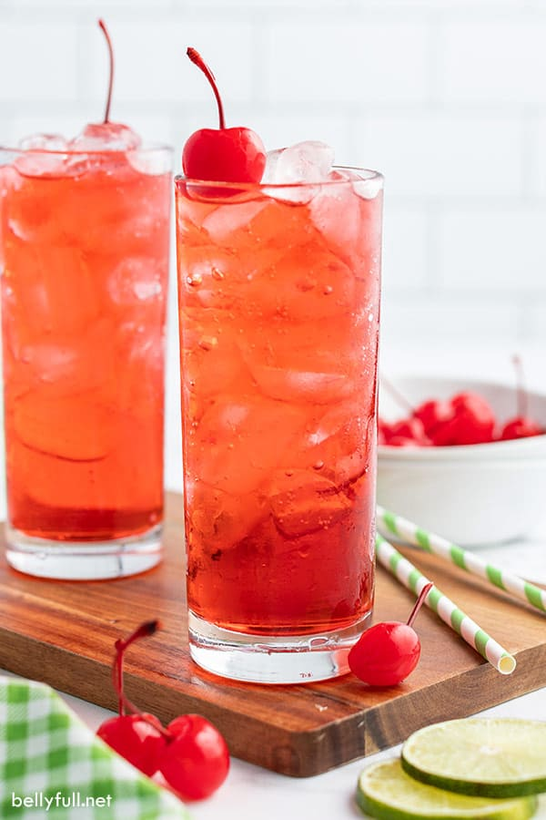 two glasses filled with soda and grenadine, garnished with a maraschino cherry