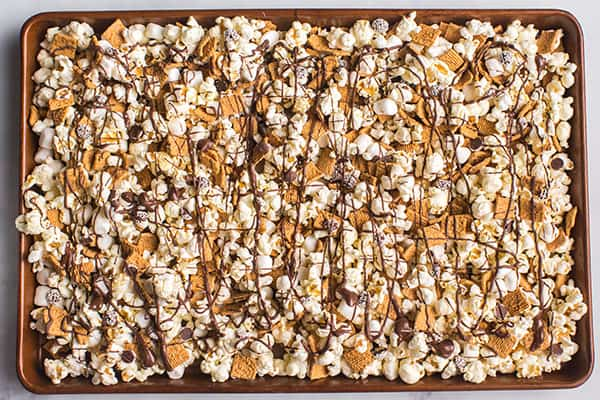 popcorn snack mix drizzled with chocolate on baking sheet