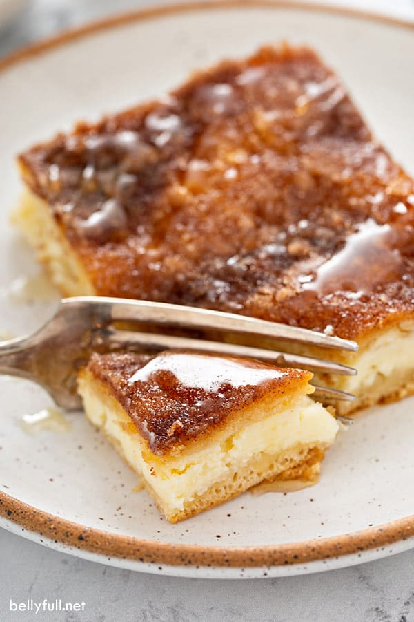 bite on fork of cheesecake bars with cinnamon-sugar crust, drizzled with honey