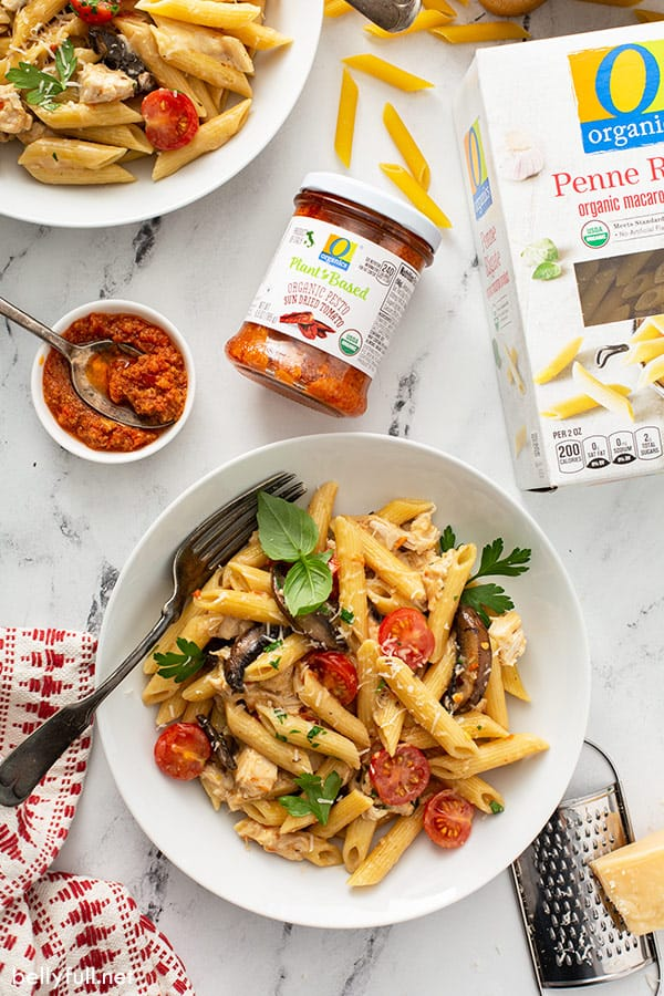 cooked penne pasta with sun dried tomato pesto in white bowl