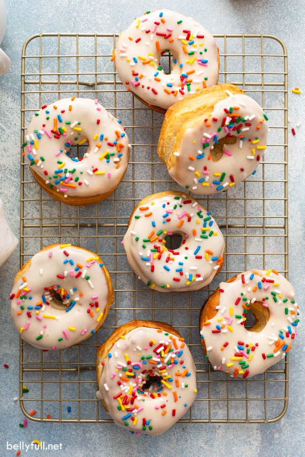 overhead of 7 donuts on cooling rack with glaze and sprinkles