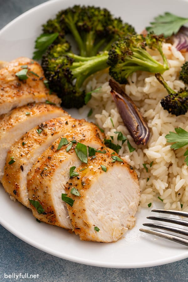 sliced baked chicken breast on white plate